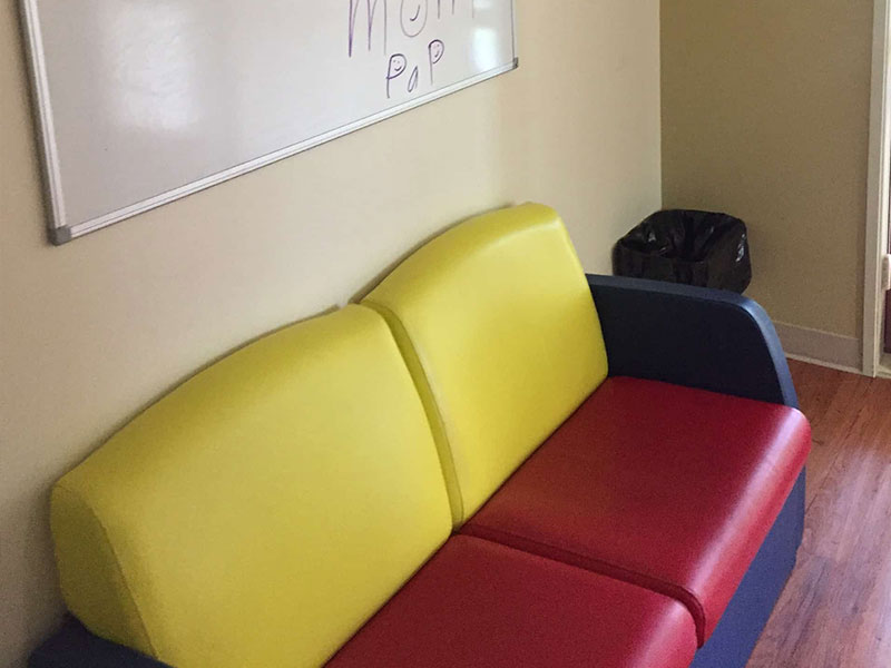 A red, yellow, and blue couch in Southwood Hospital